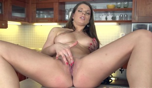 Large titted brunette plays with her pussy in the kitchen