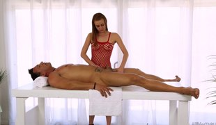 Leggy redhead masseuse milks a man's cock on the massage table