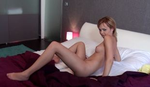 A redhead that likes to show off is on the bed, nude, jacking off