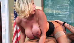 Sexy blonde teacher with huge scoops has her eyes on one of her students. She asks him to stay after class and then she shows him a good time with her pussy.