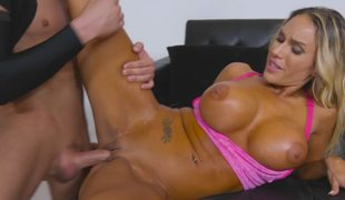 A bimbo with large tits is upside down, rammed by a hard schlong