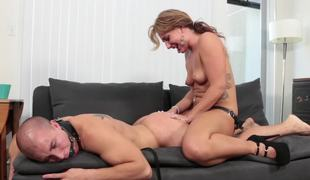 A gal is punishing her fellow by fucking him with a large strap on